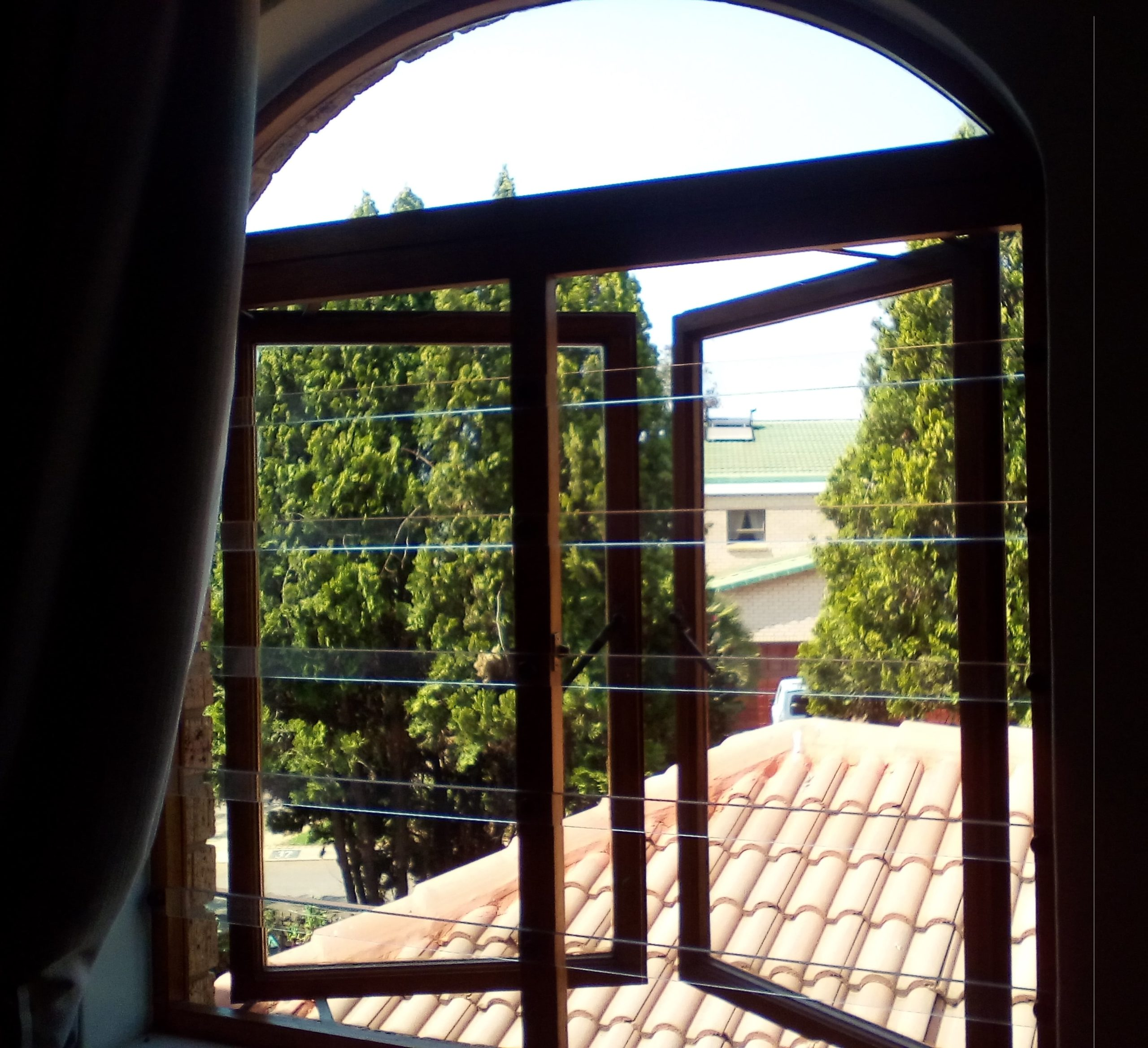 Wooden frame fitted with clear burglar bars